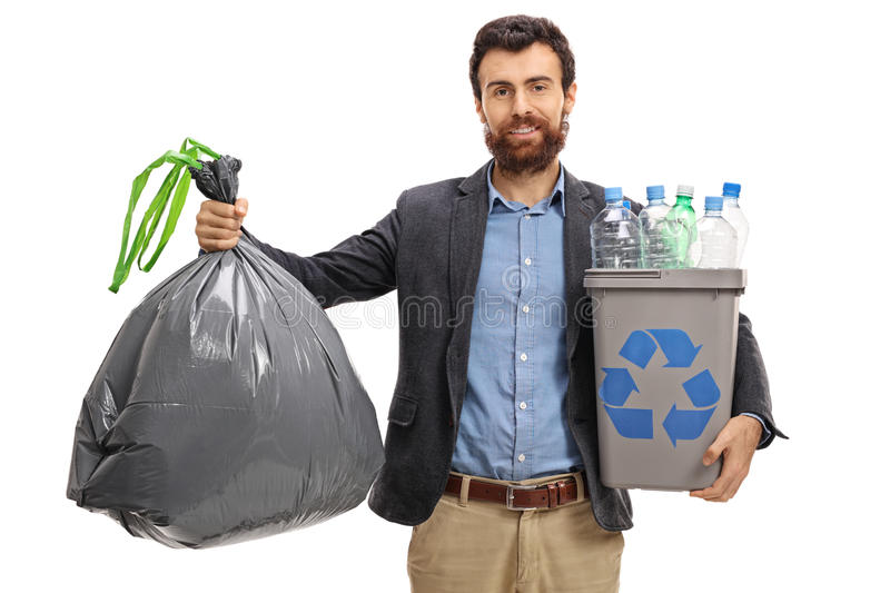 Bearded guy holding a garbage bag and a recycling bin. Full of plastic bottles isolated on white background stock photo