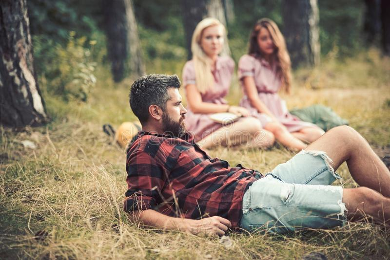 Bearded guy lying in grass on forest meadow. Girls sitting next to campfire. Friends camping in late summer. Relaxation royalty free stock images