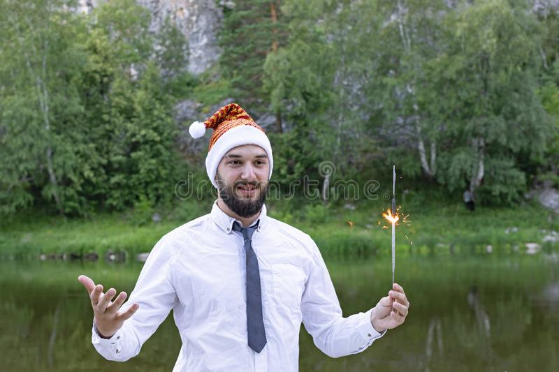 Bearded guy or man in santa hat holds a sparkler in his hands and wishes a happy new year. background summer landscape. Young bearded guy or man in santa hat royalty free stock photos