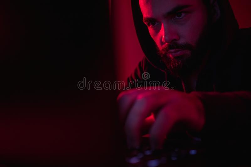 Bearded guy performing hacker attack on laptop stock image