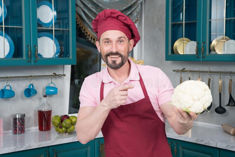 Bearded guy pointing on Cauliflower in hand. Smiling chef holds white big cauliflower in hand stock photography