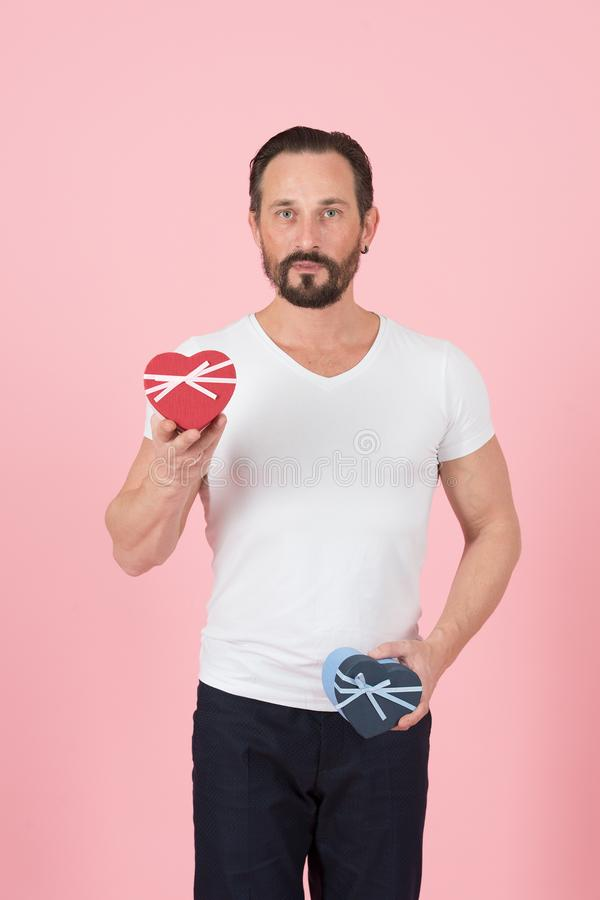 Bearded guy with red and blue hearts in hands. I prepared gift for you. Young man in white t-shirt holding gift boxes stock photos