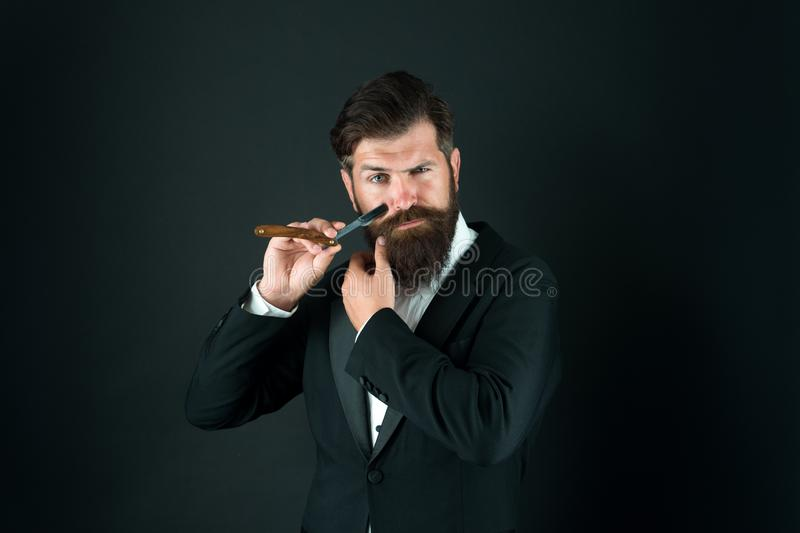 Bearded and hairy. Bearded man hold razor dark background. Businessman with bearded face. Unshaven hipster shave facial stock image
