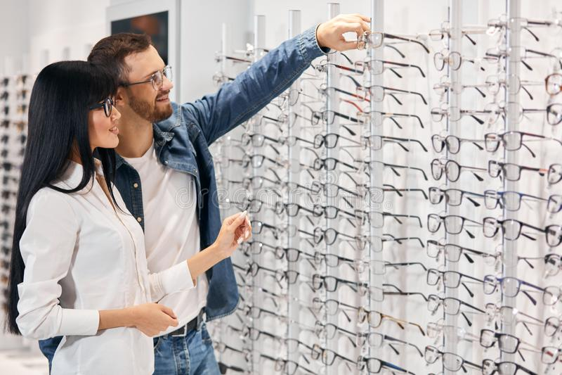Bearded handsoem smiling man taking glasses from the shelf to try them on stock images