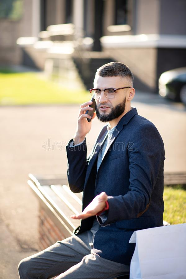 Bearded handsome businessman speaking with colleague by phone stock photo