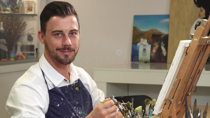 Bearded handsome cheerful artist smiling to the camera while working at his studio royalty free stock images