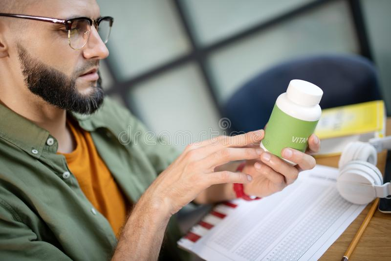 Bearded handsome man in glasses reading about vitamins. Reading about vitamins. Bearded handsome young man wearing glasses reading about vitamins royalty free stock photo