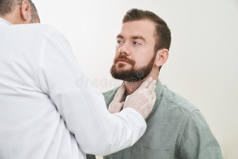 Bearded handsome man having neck and lymph nodes checked. Handsome bearded men sitting on consultation with doctor in clinic. Unrecognizable therapist wearing stock images