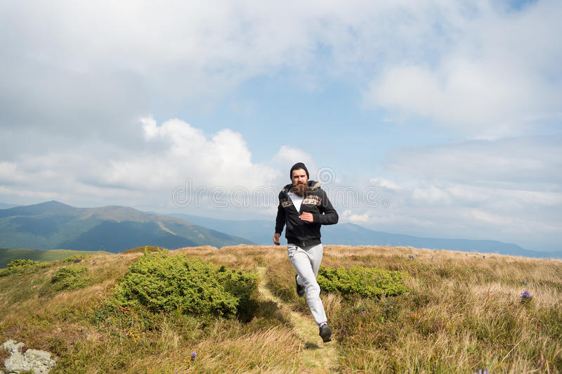 Bearded handsome man jogger run on mountain top. Handsome man hipster or guy runner with beard and moustache in hat run sunny outdoor on mountain top with green royalty free stock image