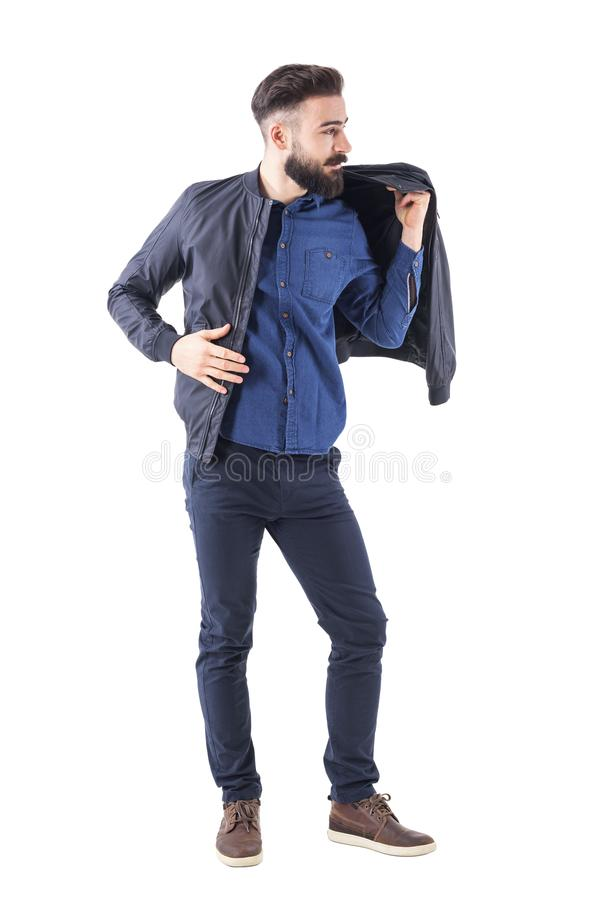 Bearded handsome man putting on bomber jacket and looking away. Full body length portrait isolated on white studio background stock image
