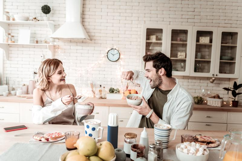 Bearded handsome positive man in a white shirt eating flakes for breakfast royalty free stock photography