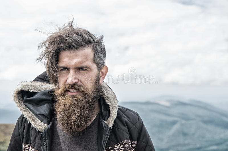 Bearded handsome serious man on mountain top. Handsome man hipster or guy with beard and moustache on serious face in hat and jacket outdoor on mountain top stock photo