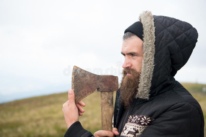 Bearded handsome serious man with rusty axe on mountain top. Handsome man hipster or guy with beard and moustache on serious face in hat and jacket holds rusty royalty free stock image