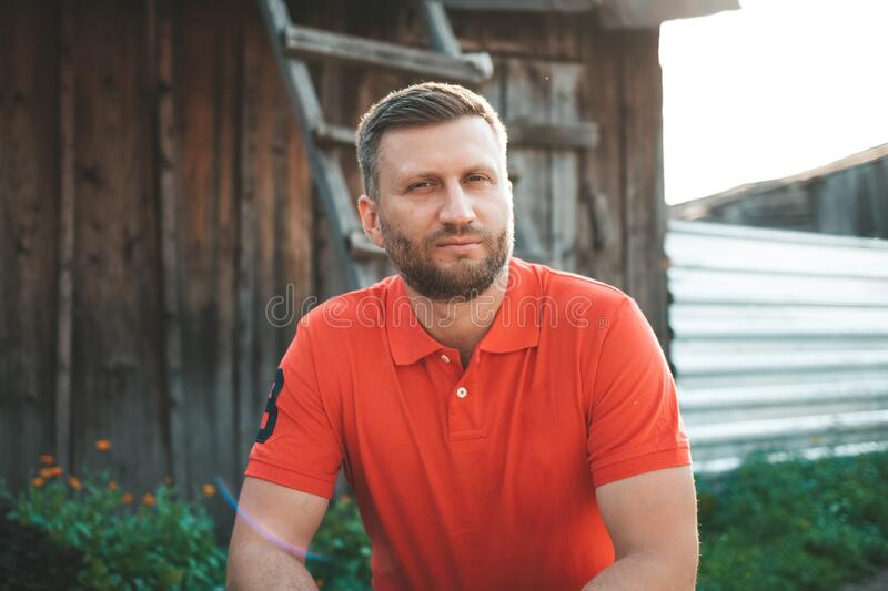 Bearded handsome stylish man in a red polo. Brutal man looks in a frame at a wooden building. Solar back light. Well-groomed serio stock image