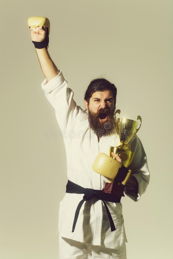 Bearded happy karate man in kimono, boxing gloves, champion cup. Bearded karate man, long beard, brutal caucasian hipster with moustache in white kimono with stock photo