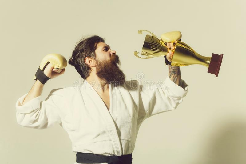 Bearded happy karate man in kimono, boxing gloves, champion cup. Bearded karate man, long beard, brutal caucasian hipster with moustache in white kimono with royalty free stock image