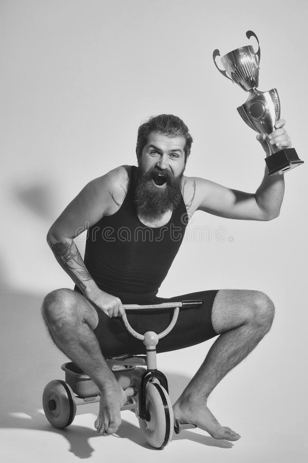 Bearded happy man holds gold champion cup on bicycle toy. Bearded man, long beard, brutal caucasian hipster with moustache in black vest holds gold champion cup royalty free stock photography