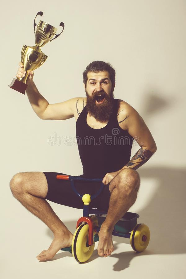 Bearded happy man holds gold champion cup on bicycle toy. Bearded man, long beard, brutal caucasian hipster with moustache in black vest holds gold champion cup stock image