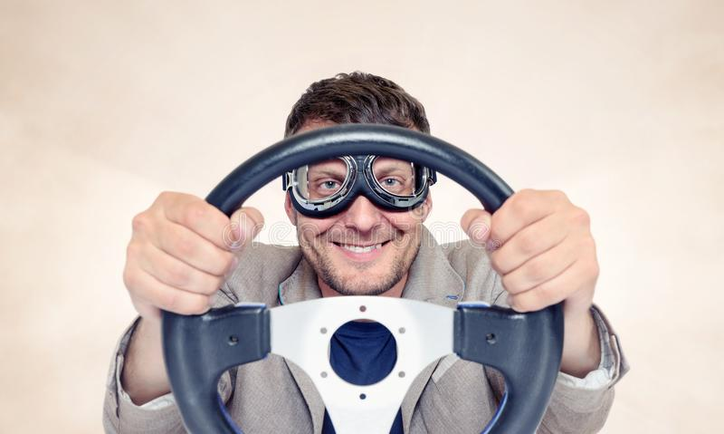Bearded happy man in stylish goggles with steering wheel on background, car driver concept royalty free stock photo