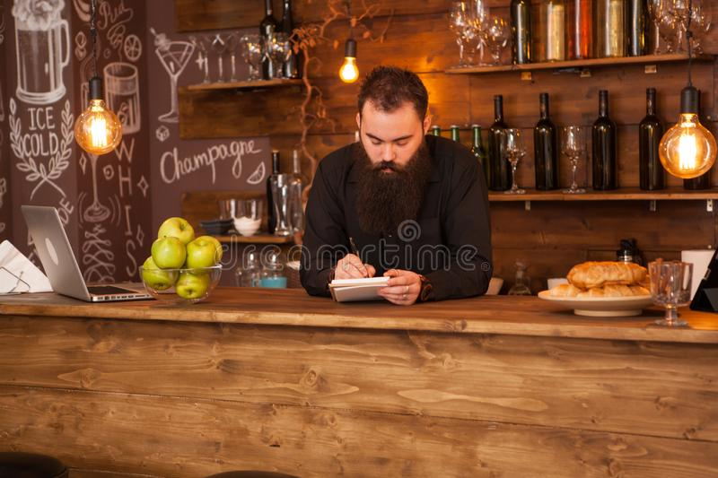 Bearded hipster bartender taking notes in vintage pub royalty free stock images