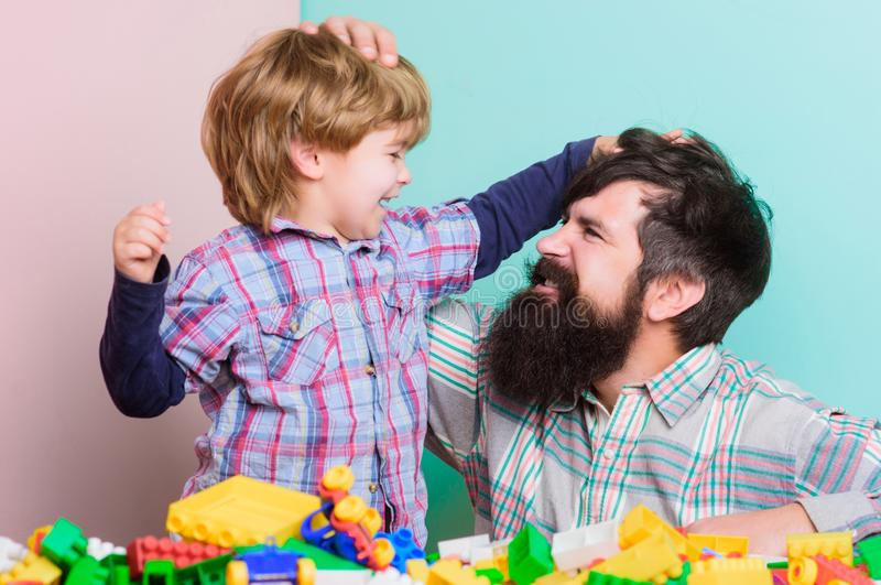 Bearded hipster and boy play together. Dad and child build of plastic blocks. Happy childhood. Child care concept. Happy royalty free stock image