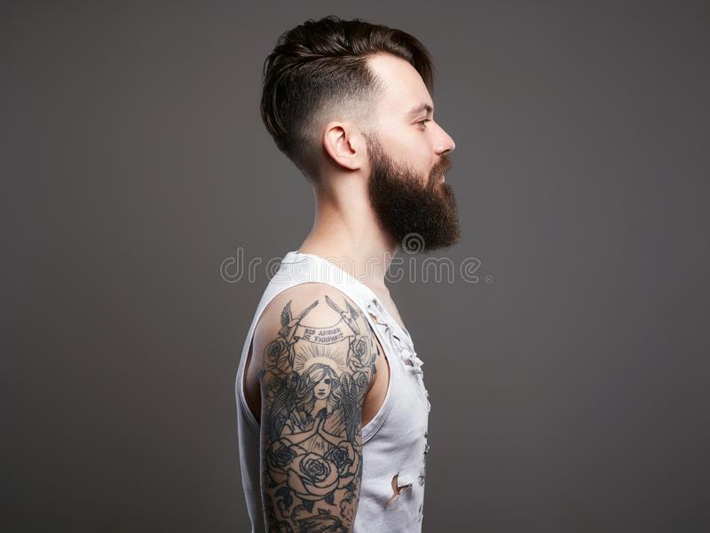 Bearded hipster boy in vintage torn dirty shirt. Handsome man with beard and tattoo. bearded hipster boy in vintage torn dirty shirt royalty free stock photos