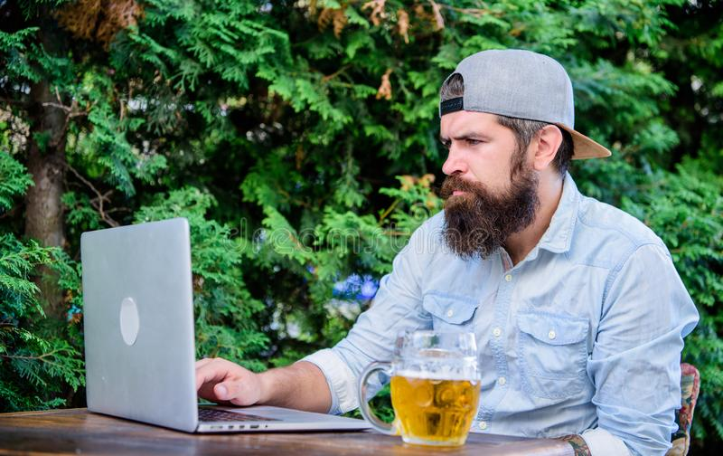 Bearded hipster freelancer enjoy end of working day with beer mug. Beer helps him relax after hard day. Brutal man royalty free stock image
