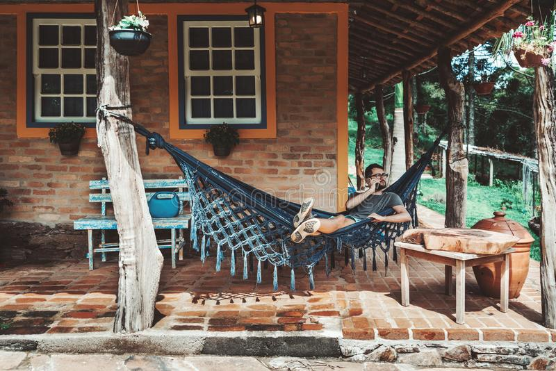 Bearded hipster guy in glasses in hammock outdoors phoning royalty free stock photos