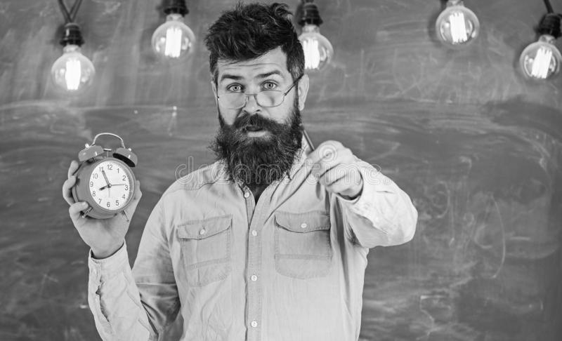 Bearded hipster holds clock, chalkboard on background. Man with beard and mustache on surprised face. Teacher in. Eyeglasses holds alarm clock and pointing royalty free stock images