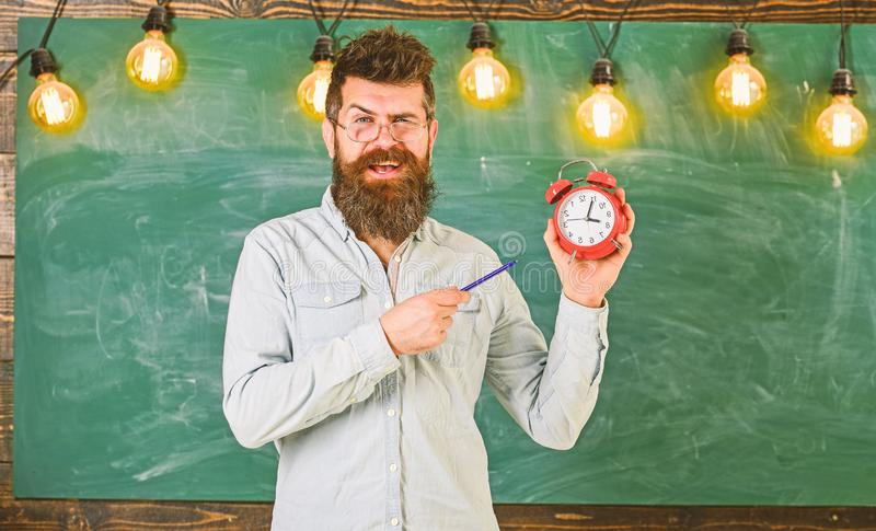 Bearded hipster holds clock, chalkboard on background. . Teacher in eyeglasses holds alarm clock and pen. Discipline. Concept. Man with beard and mustache on royalty free stock photography