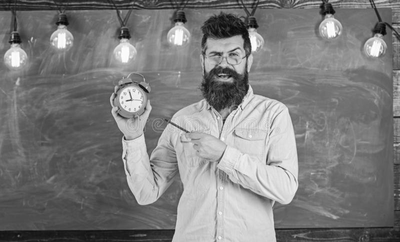 Bearded hipster holds clock, chalkboard on background. . Teacher in eyeglasses holds alarm clock and pen. Discipline. Concept. Man with beard and mustache on royalty free stock images