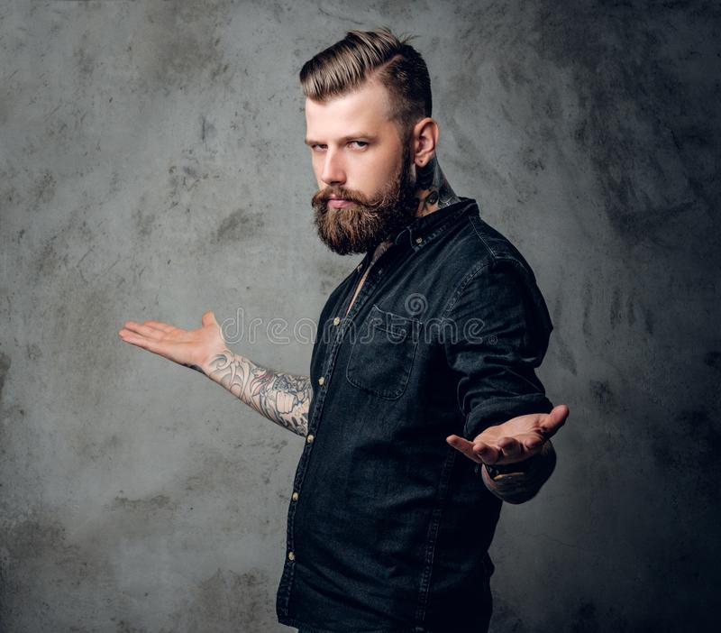 Bearded hipster male in a black shirt. Stylish tattooed, bearded hipster male in a black shirt posing on grey background stock photos