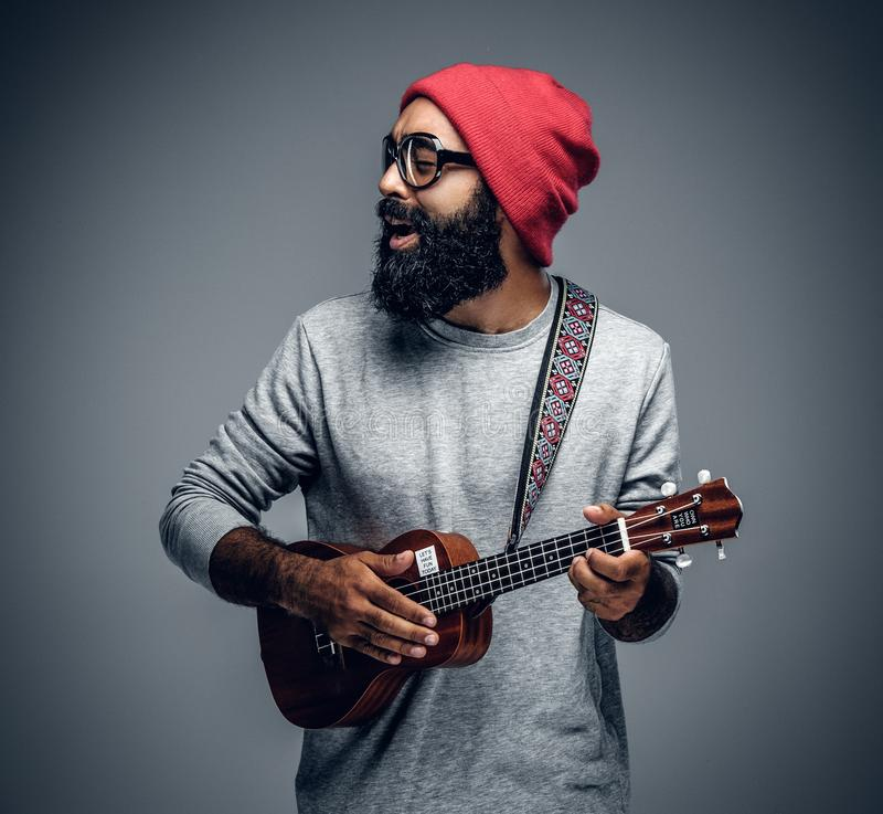 Bearded hipster male in red hat playing on ukulele. Portrait of a bearded hipster male in red hat playing on ukulele. on grey background royalty free stock photos