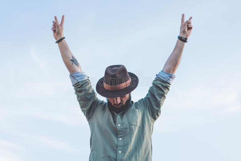 Bearded Hipster male wearing fashion hat, enjoying view of blue and clear sky with raised his hands up victory symbol. Bearded Hipster male wearing fashion hat royalty free stock photo