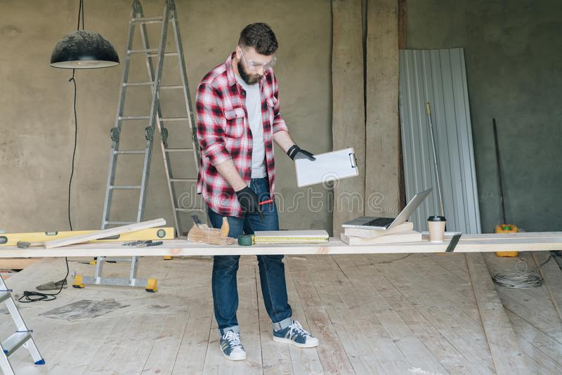 Bearded hipster man is carpenter, builder, designer stands in workshop,holds clipboard and hammer, reads instruction stock photo