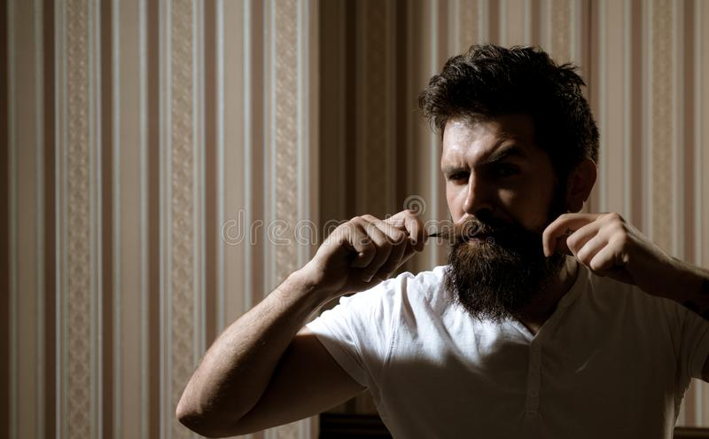 Bearded hipster man holding his long moustache. Bath procedures and grooming. Brutal muscular man going to shave his stock photography