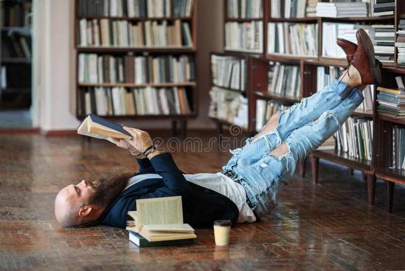 Bearded hipster man relax and reading book lies on the floor. In library royalty free stock photos