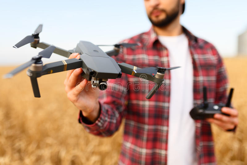 Bearded hipster man shows small compact drone and holds remote controller in his hand. Farmer agronomist looks at royalty free stock image