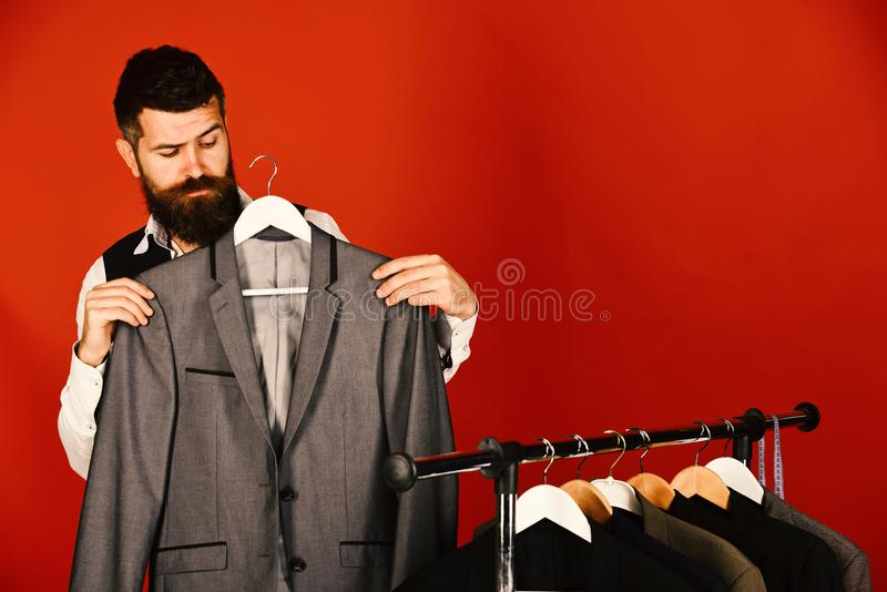 Bearded hipster man stands near rack with clothes royalty free stock image