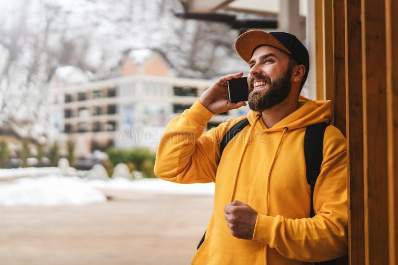 Bearded hipster man tourist in yellow hoodie and cap stands outdoors, talking on mobile phone. Smiling man calling friends royalty free stock images