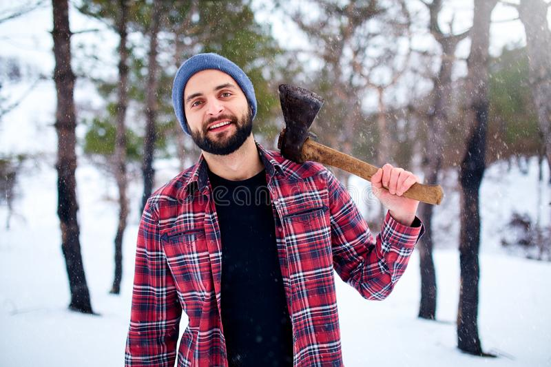 Bearded hipster man in a winter snowy forest with axe on a shoulder. Woodman standing in the forest. Male inspecting stock image