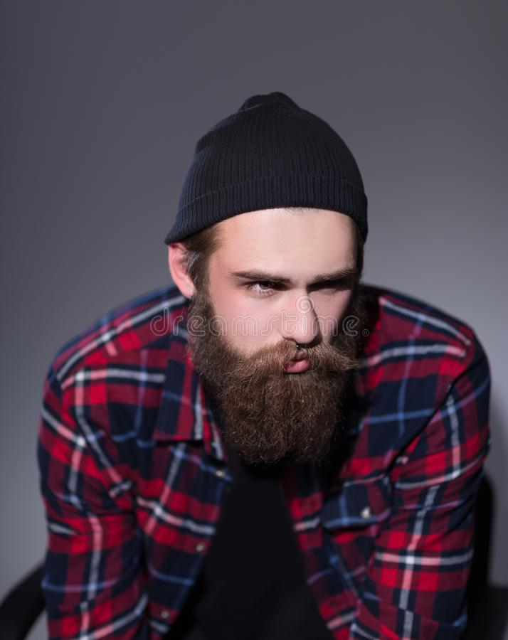 Bearded hipster in plaid shirt looking away. stock photos