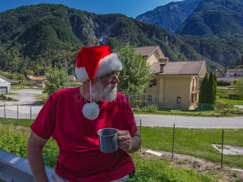 Bearded hipster in red shirt and hat of Santa Claus drinking from large mug stock image