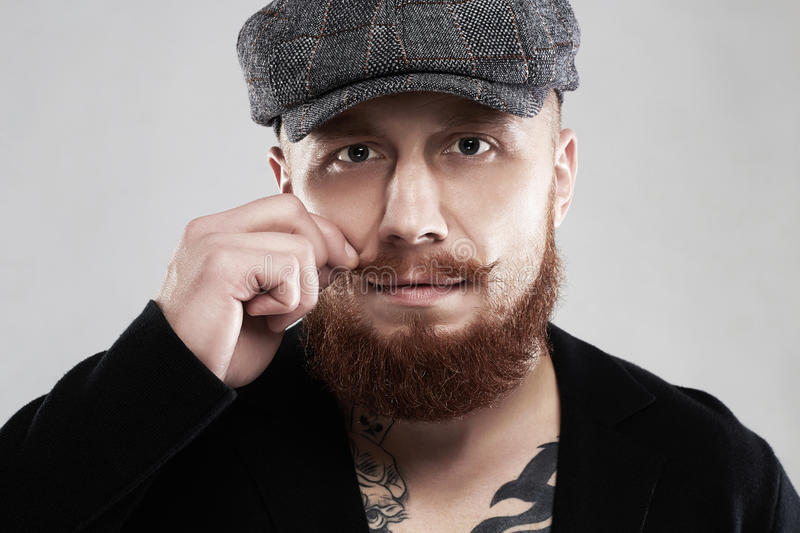Bearded hipster with tattoo.brutal handsome boy in hat. Close-up male face with mustache and beard.bearded hipster with tattoo.brutal handsome boy in hat royalty free stock photos