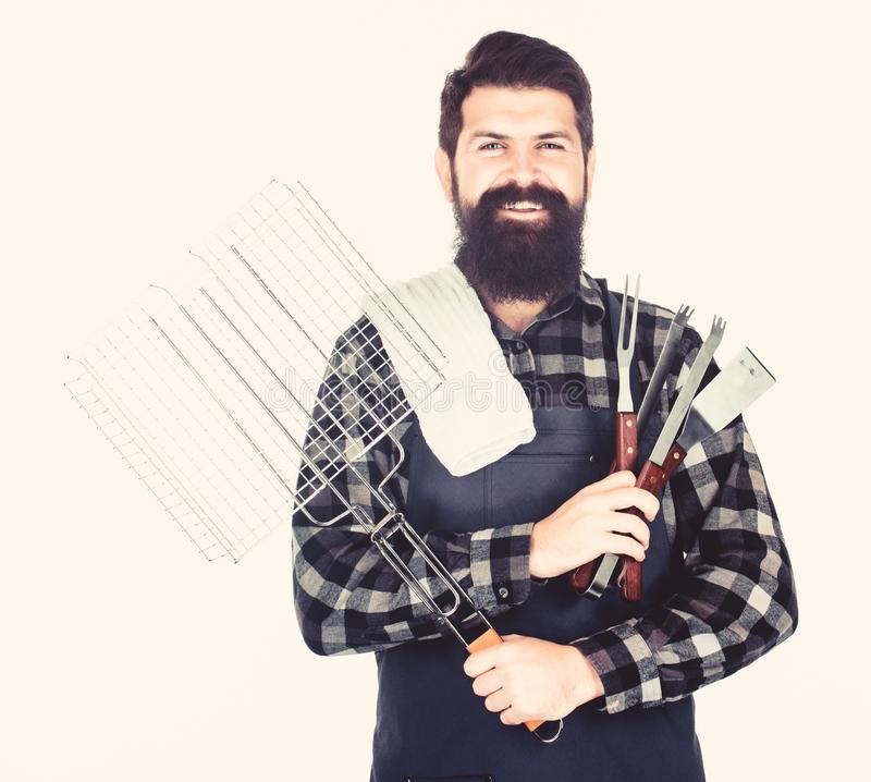 Bearded hipster wear apron for barbecue. Roasting and grilling food. Man hold cooking utensils barbecue. Tools for stock photography