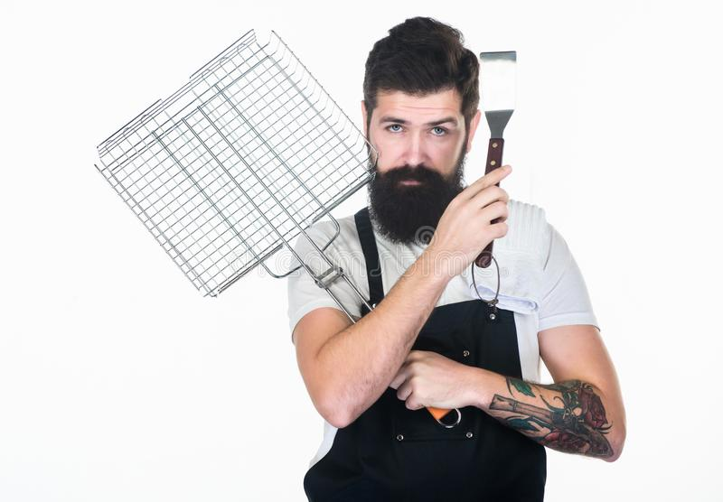 Bearded hipster wear apron for barbecue. Roasting and grilling food. Tips cooking meat. Tools for roasting meat outdoors royalty free stock photography