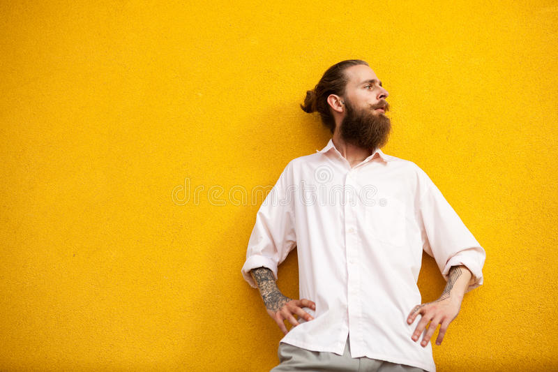 Bearded hipster on yellow vintage wall stock image