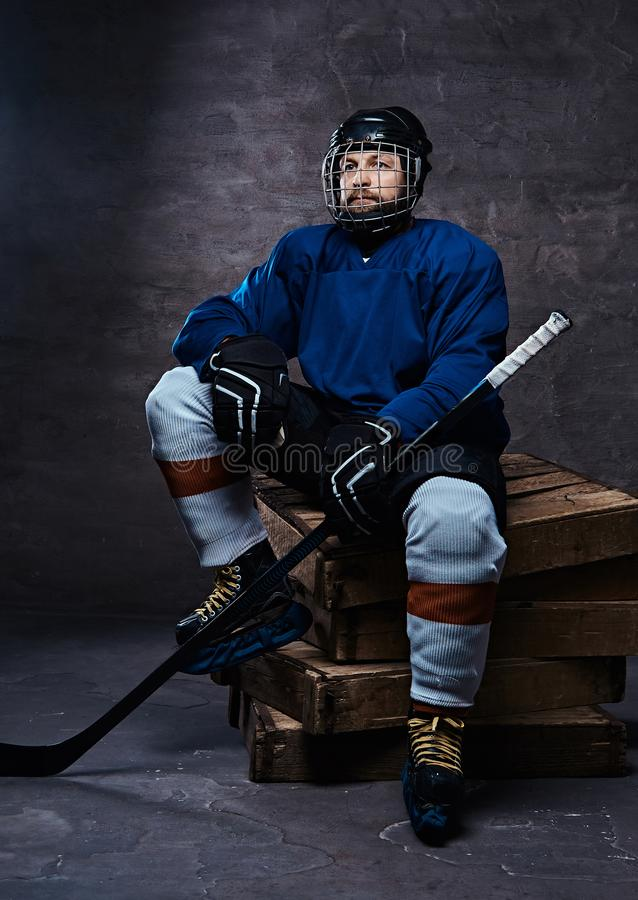 Portrait of a bearded hockey player wearing full sports equipment holding a hockey stick while sitting on wooden pallets royalty free stock photo