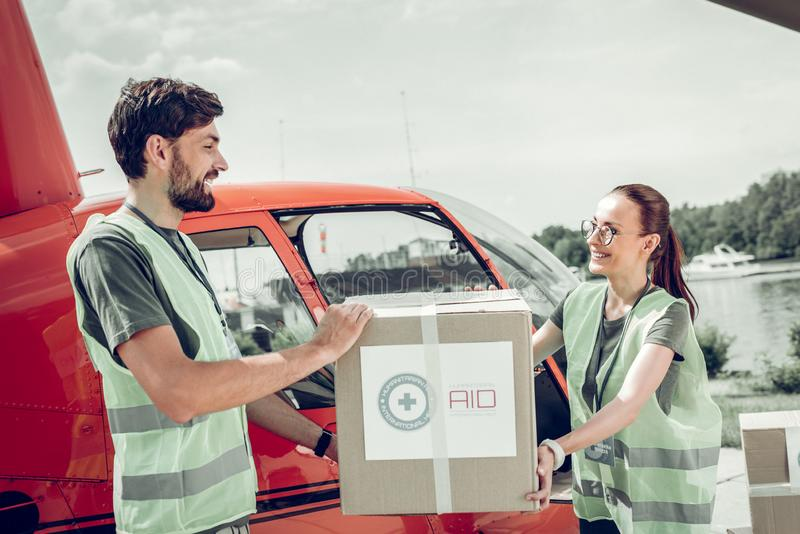 Bearded humanitarian worker helping his colleague holding heavy box. Helping colleague. Bearded humanitarian worker helping his colleague holding heavy box while stock images