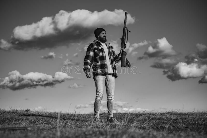 Bearded hunter man holding gun and walking in forest. Hunter with shotgun gun on hunt. royalty free stock photos